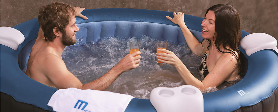 Zwei Personen baden im MSpa Comfort Bergen C-BE061 Whirlpool und konsumieren einen Softdrink bei heißem Sommerwetter